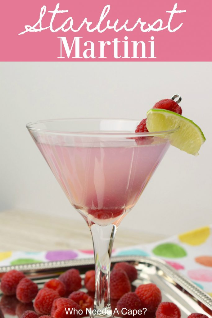 pink starburst martini with lime and raspberry garnish in glass on silver platter with polka dot fabric underneath