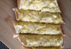 This Loaded Artichoke Garlic Bread is chock full of cheesy goodness. Perfect with pasta or as an appetizer! Delish!