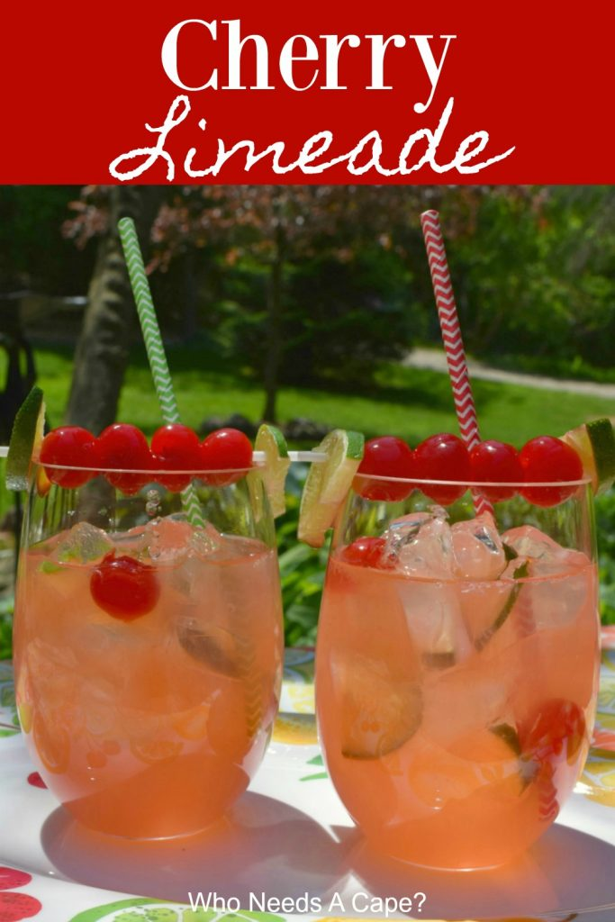 Two glasses of cherry limeade with cherry and lime garnish and straws on fruit patterened platter outdoors