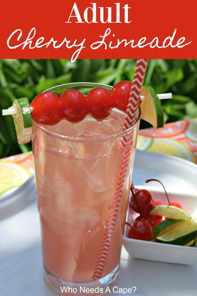 glass of adult cherry limeade on white platter outdoors