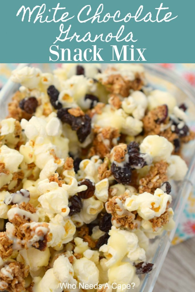 white chocolate granola snack mix in container on colorful fabric