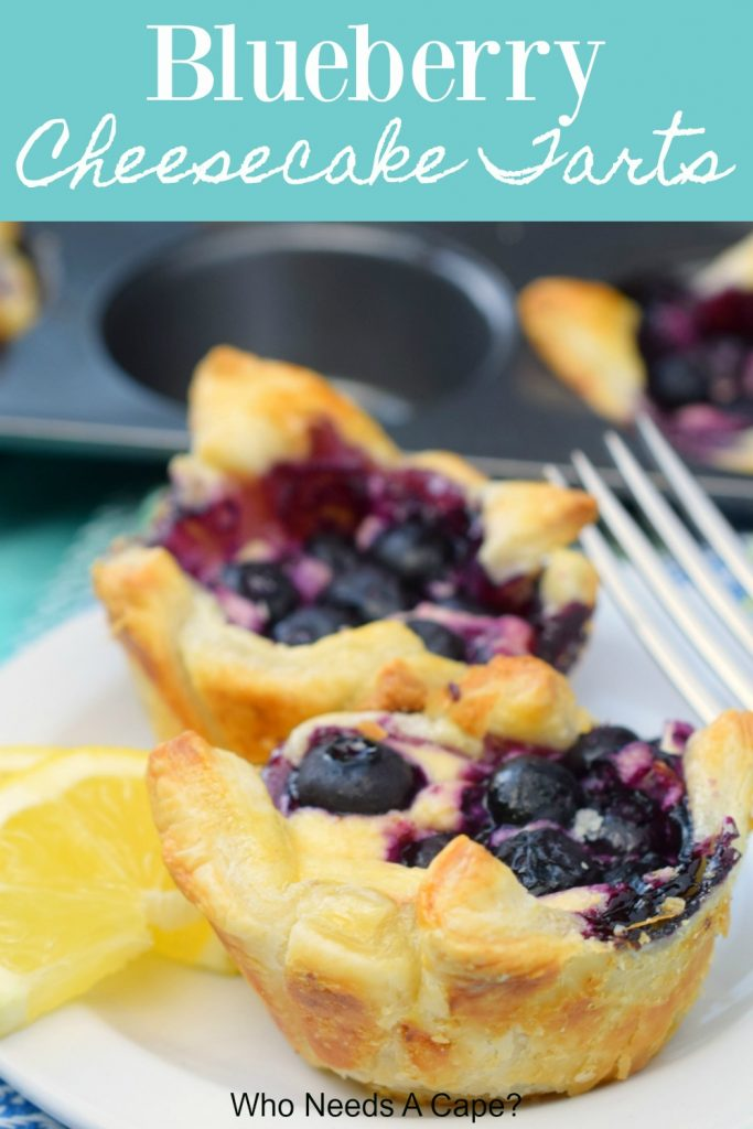 blueberry cheesecake tarts on plate with fork with lemon slices next to baking pan