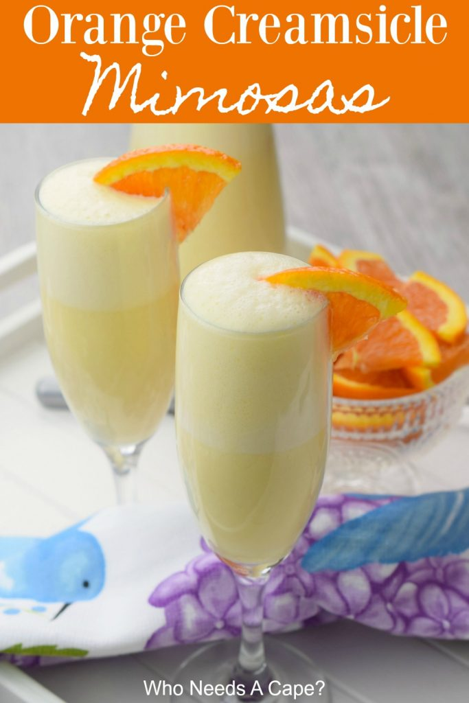 orange creamsicle mimosas in champagne flutes with orange slice garnish next to carafe and bowl of sliced oranges on floral fabric and white tray