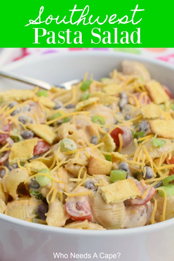 white bowl of southwest pasta salad with spoon on polka dot fabric